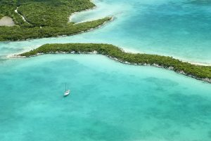 Blue Caribbean sea, yacht and island on bahamas yacht charter
